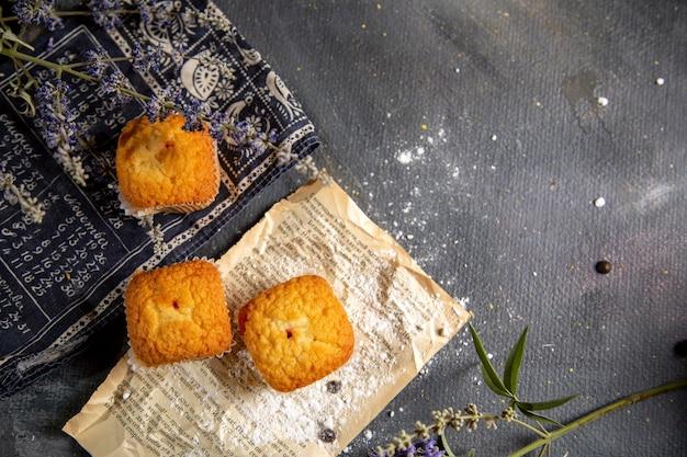 Een bovenaanzicht van heerlijke kleine cakes met paarse bloemen