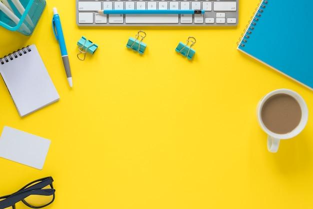 Een bovenaanzicht van het toetsenbord; bril en kopje thee op gele werkruimte