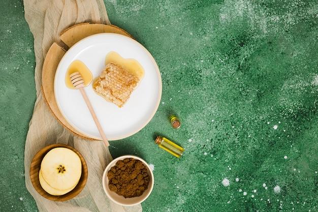 Een bovenaanzicht van honingraat op keramische plaat met plakjes appel; etherische olie en koffiedik tegen groene gestructureerde achtergrond