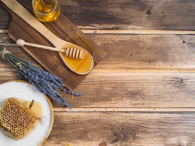 Een bovenaanzicht van honingraatstuk; lavendel en honing op houten tafel