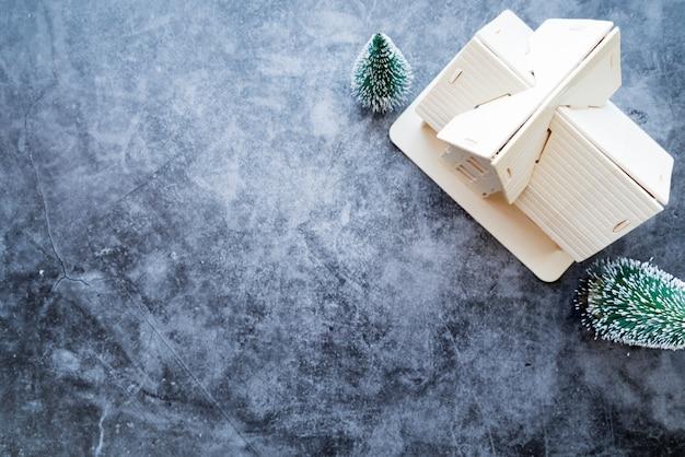 Een bovenaanzicht van huis-model met kerstboom op verweerde concrete achtergrond