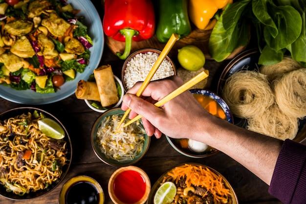 Een bovenaanzicht van iemands hand met stokjes over het heerlijke thais eten