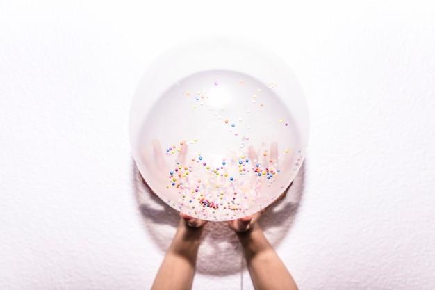 Een bovenaanzicht van iemands hand met witte ballon met kleurrijke strooi op witte gestructureerde achtergrond