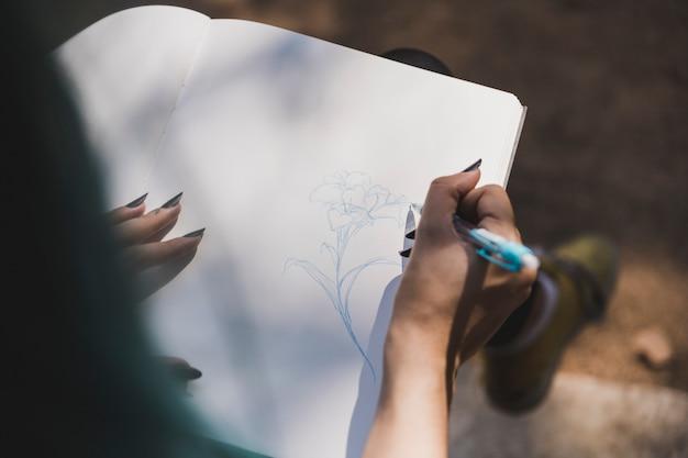 Een bovenaanzicht van iemands hand tekening bloem op notebook