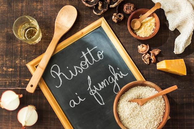 Een bovenaanzicht van ingrediënten voor het maken van risotto funghi geschreven op leisteen met krijt