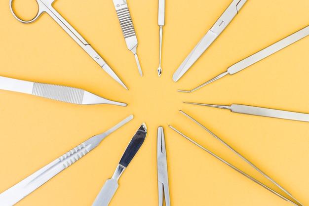 Een bovenaanzicht van instrumenten voor plastische chirurgie op gele achtergrond