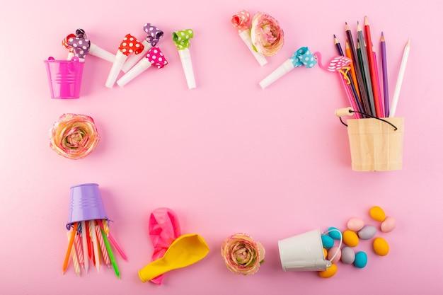 Een bovenaanzicht van kaarsen en potloden samen met ballen en snoepjes overal in het roze snoep van de kleurenfoto van het bureau