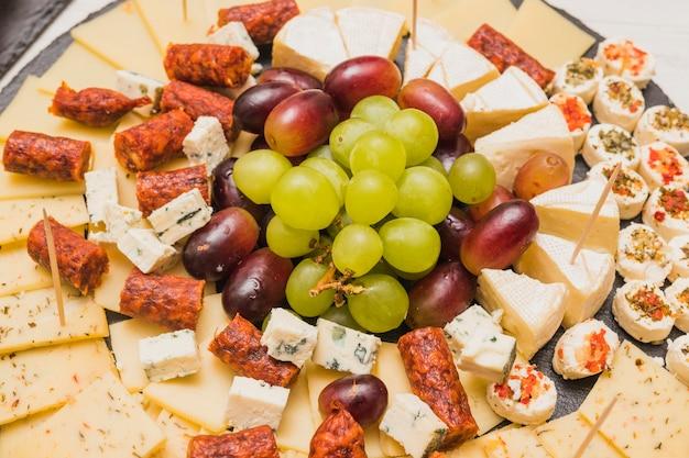 Een bovenaanzicht van kaasplateau; druiven en rookworst