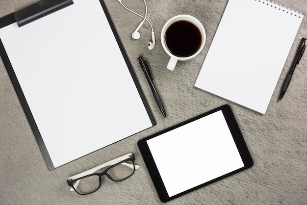 Een bovenaanzicht van kantoorbenodigdheden met koffiekopje en digitale tablet op grijs bureau