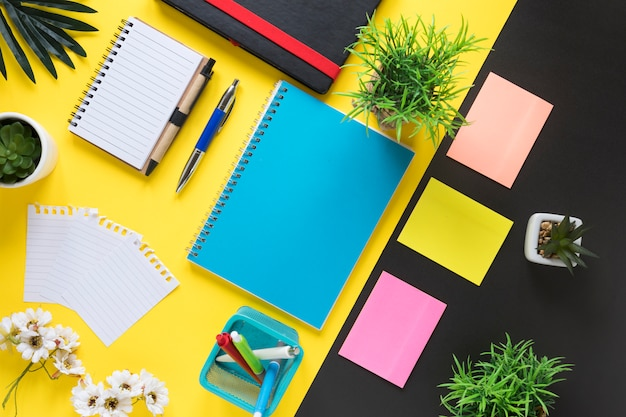 Een bovenaanzicht van kantoorbenodigdheden op gele en zwarte achtergrond
