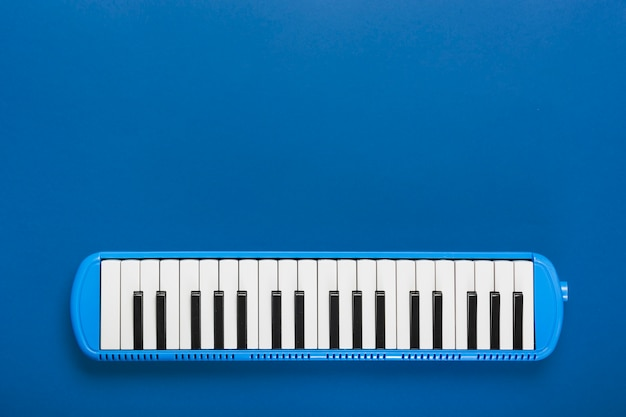 Een bovenaanzicht van klassieke piano zwart en wit toetsenbord op blauwe achtergrond