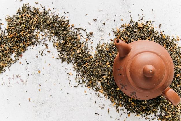 Een bovenaanzicht van klei theepot op droge thee kruiden over de concrete achtergrond