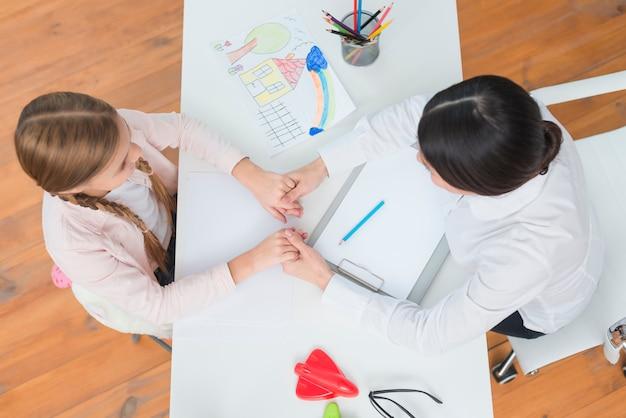 Een bovenaanzicht van klein meisje en vrouwelijke psycholoog houden elkaars hand op witte tafel