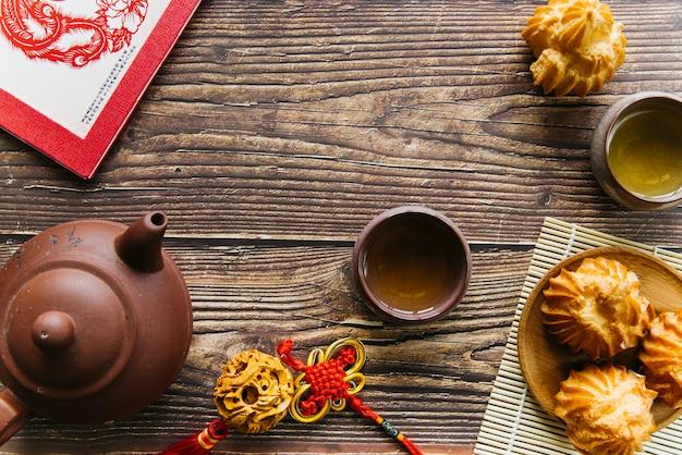 Een bovenaanzicht van kleitheepot en theekopjes met zelfgemaakte kokoskoekjes over de houten tafel