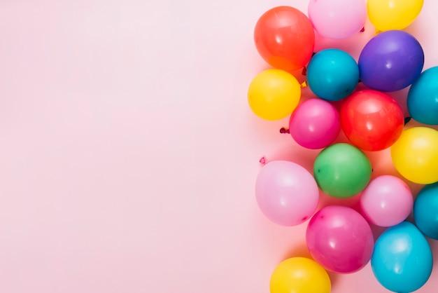 Een bovenaanzicht van kleurrijke ballonnen over roze achtergrond