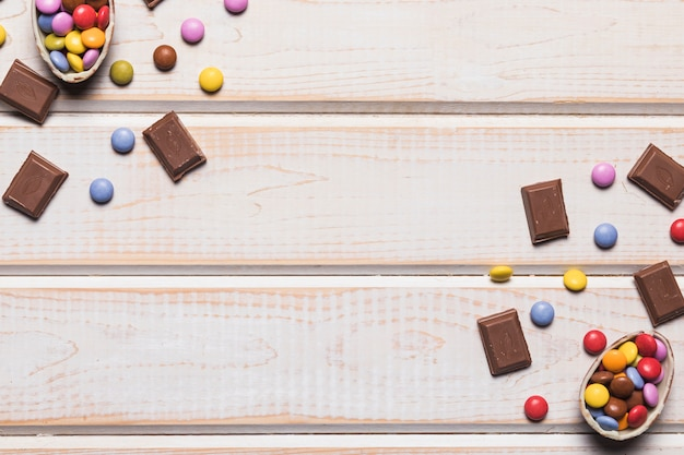 Een bovenaanzicht van kleurrijke edelstenen en chocoladestukjes op houten bureau