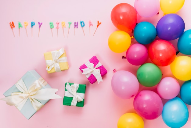 Een bovenaanzicht van kleurrijke geschenkdozen; ballonnen en gelukkige verjaardag kaarsen op roze achtergrond