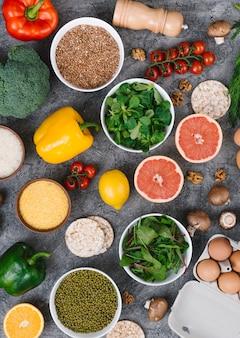 Een bovenaanzicht van kleurrijke groenten en fruit op concrete achtergrond