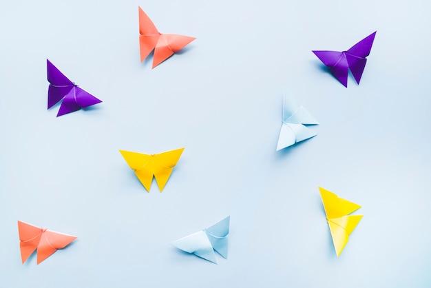 Een bovenaanzicht van kleurrijke origami papier vlinders op blauwe achtergrond