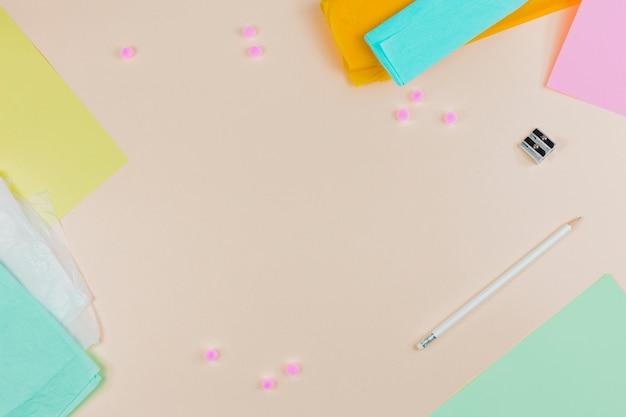 Een bovenaanzicht van kleurrijke papieren met puntenslijper en wit potlood op beige achtergrond