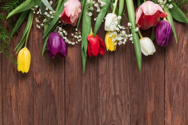 Een bovenaanzicht van kleurrijke tulpen en baby's adem bloem op houten bureau