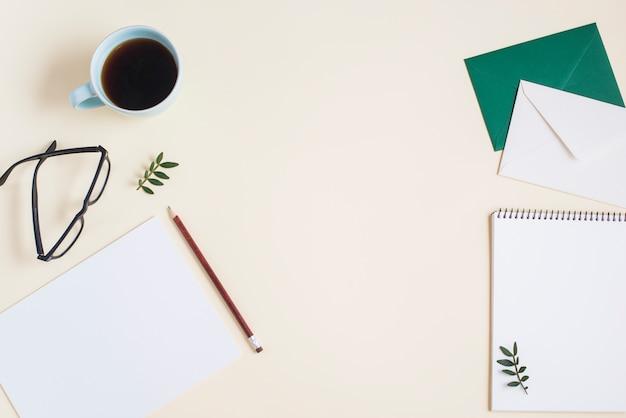 Een bovenaanzicht van koffiekopje; brillen en stationeries op beige achtergrond