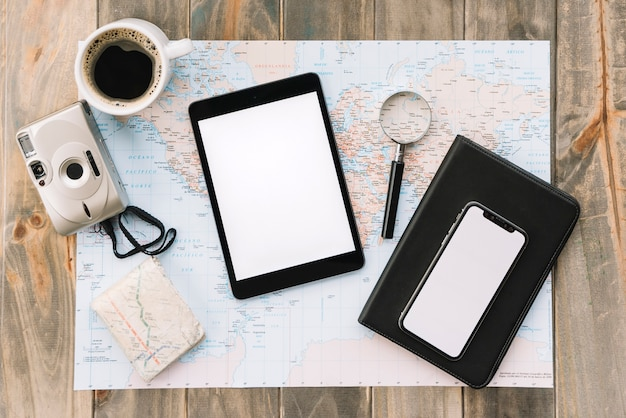 Een bovenaanzicht van koffiekopje; camera; digitale tablet; mobiele telefoon; vergrootglas en dagboek op kaart tegen houten tafel