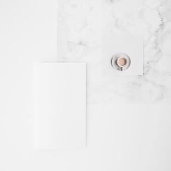 Een bovenaanzicht van koffiekopje en blanco papier op bureau tegen een witte achtergrond