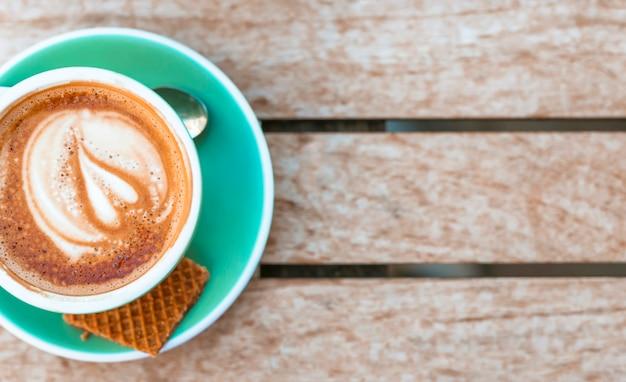 Een bovenaanzicht van koffiekopje met hart latte kunst op houten tafel