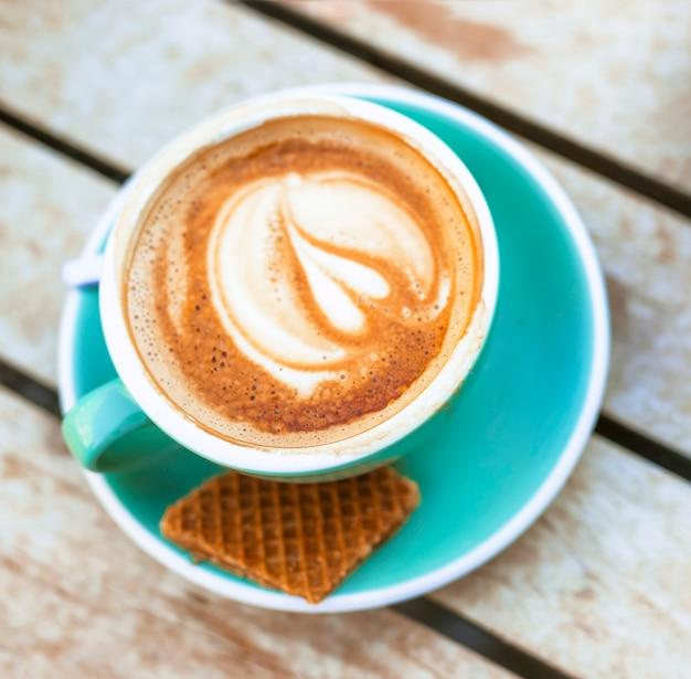Een bovenaanzicht van koffiekopje met latte art en wafel hartvorm
