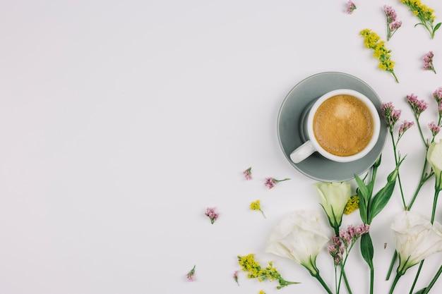 Een bovenaanzicht van koffiekopje met limonium; eustoma en guldenroede op witte achtergrond