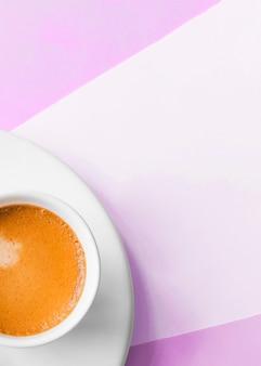 Een bovenaanzicht van koffiekopje op roze achtergrond