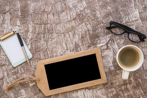 Een bovenaanzicht van koffiekopje; pen; klein klembord en bril op gestructureerde achtergrond