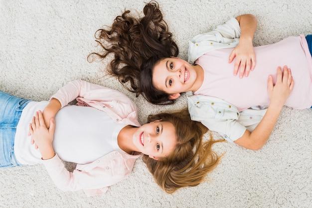 Een bovenaanzicht van lachende twee meisjes ontspannen op witte tapijt