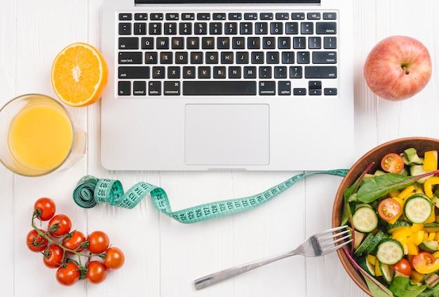 Een bovenaanzicht van laptop met frisse salade; vruchten; sap en cherry tomaten op witte houten bureau