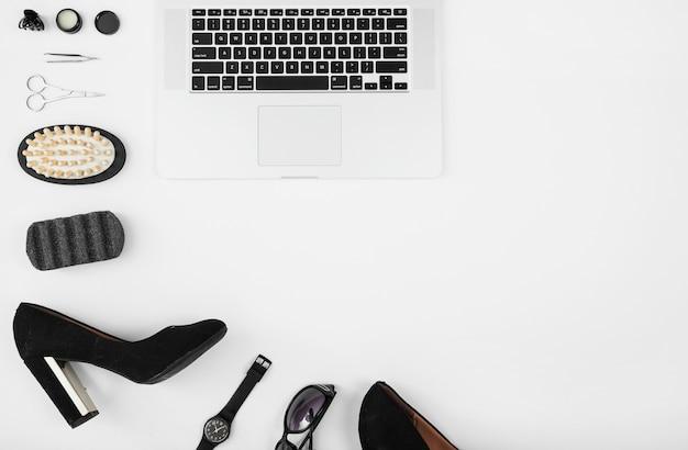 Een bovenaanzicht van laptop met vrouwelijke accessoires tegen een witte achtergrond