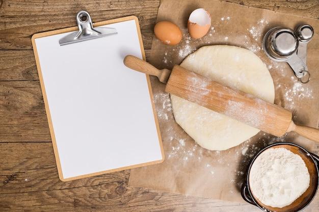 Een bovenaanzicht van leeg witboek op klembord met platte deeg klaar voor bakken op perkamentpapier over de houten tafel