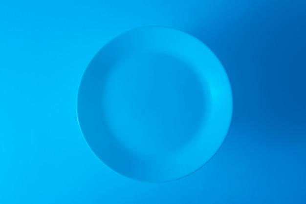 Een bovenaanzicht van lege blauwe plaat tegen blauwe achtergrond