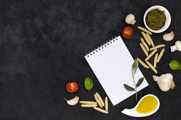 Een bovenaanzicht van lege spiraal kladblok met italiaanse pasta ingrediënten tegen zwarte gestructureerde achtergrond