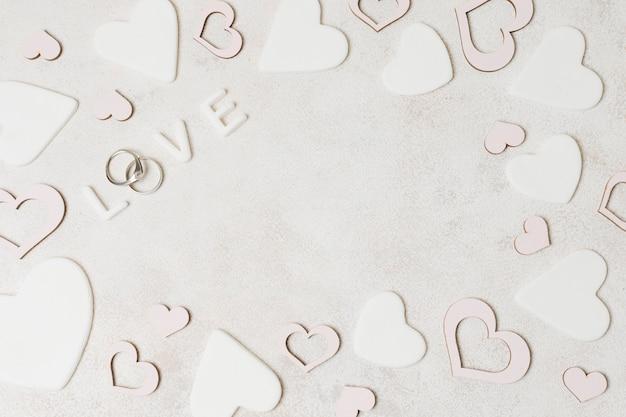 Een bovenaanzicht van liefdetekst met diamanten trouwringen omringd met roze en witte hartvorm