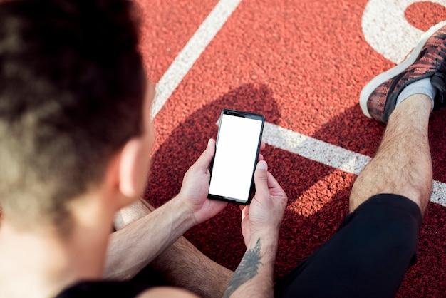 Een bovenaanzicht van mannelijke atleet zittend op racebaan met behulp van de mobiele telefoon