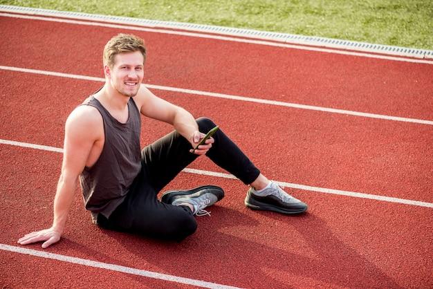 Een bovenaanzicht van mannelijke atleet zittend op rode racebaan mobiele telefoon in de hand houden