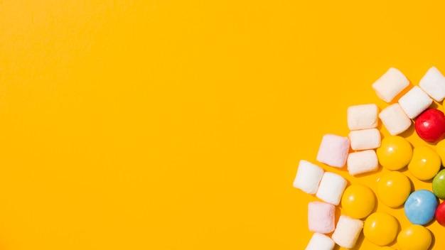 Een bovenaanzicht van marshmallow en kleurrijke snoepjes op gele achtergrond