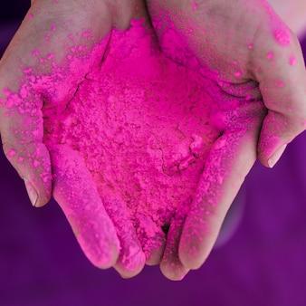 Een bovenaanzicht van menselijke hand met roze holi kleur
