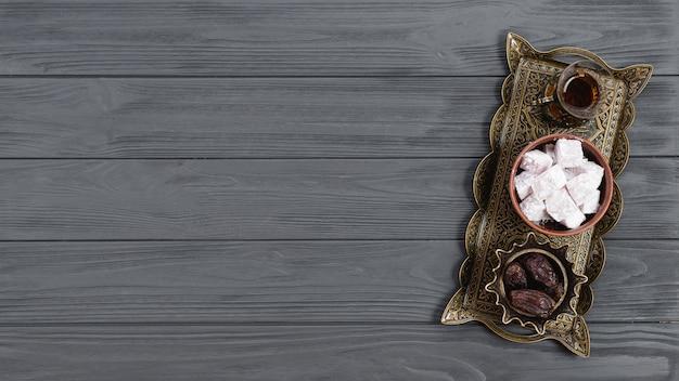 Een bovenaanzicht van metalen dienblad met lukum van turkse verrukking; dadels en thee op ramadan over de houten tafel