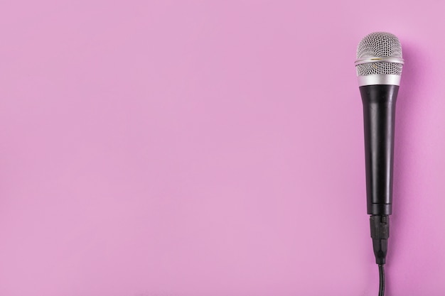 Een bovenaanzicht van microfoon op roze achtergrond