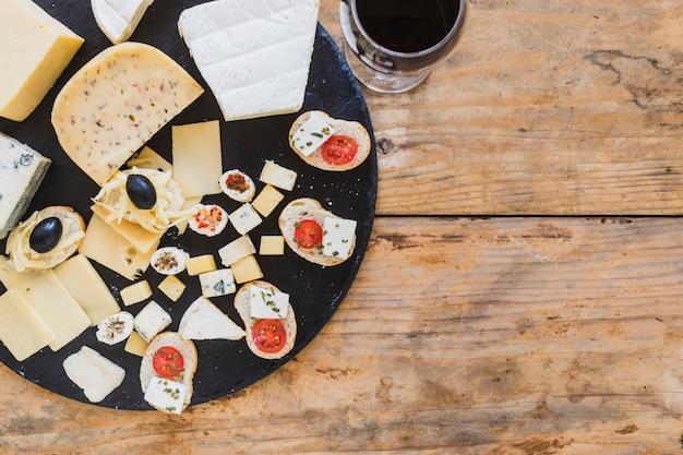 Een bovenaanzicht van mini-broodjes met kaas en tomaten op houten bureau