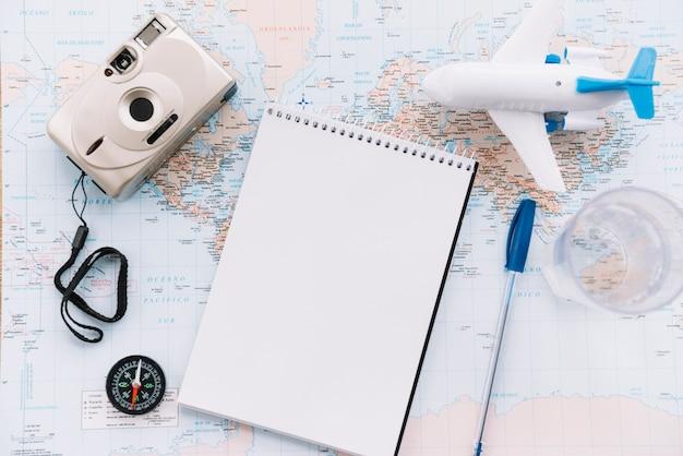 Een bovenaanzicht van miniatuur wit vliegtuig; spiraal lege blocnote; pen; camera en kompas op de kaart