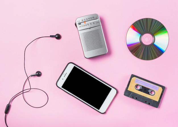 Een bovenaanzicht van mobiel met oortelefoon; cd; radio en cassette op roze achtergrond