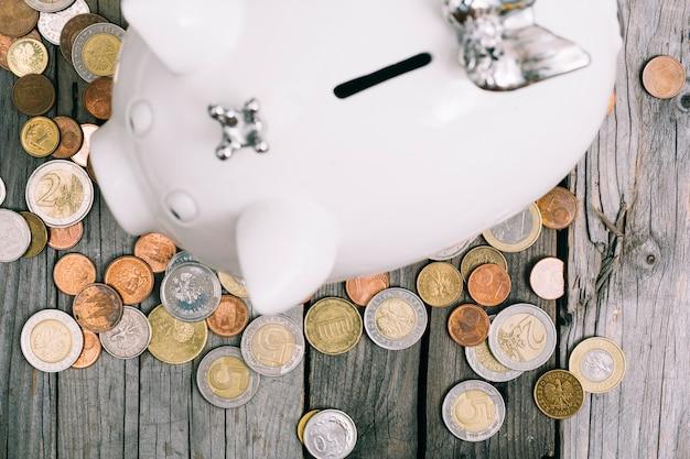 Een bovenaanzicht van munten rond de witte spaarpot op houten tafel